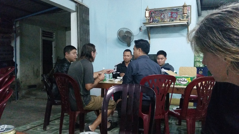 bike touring ho chi minh trail eating and drining with policemen